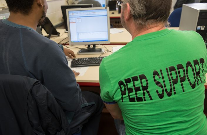 Prison peer mentor helping another man to access a computer